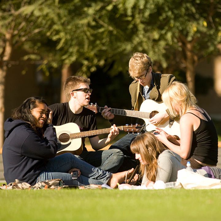 音乐 students playing guitars and doing homework in Sunken Garden