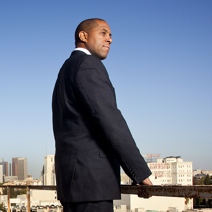 Man standing on a city rooftop with skyline in background